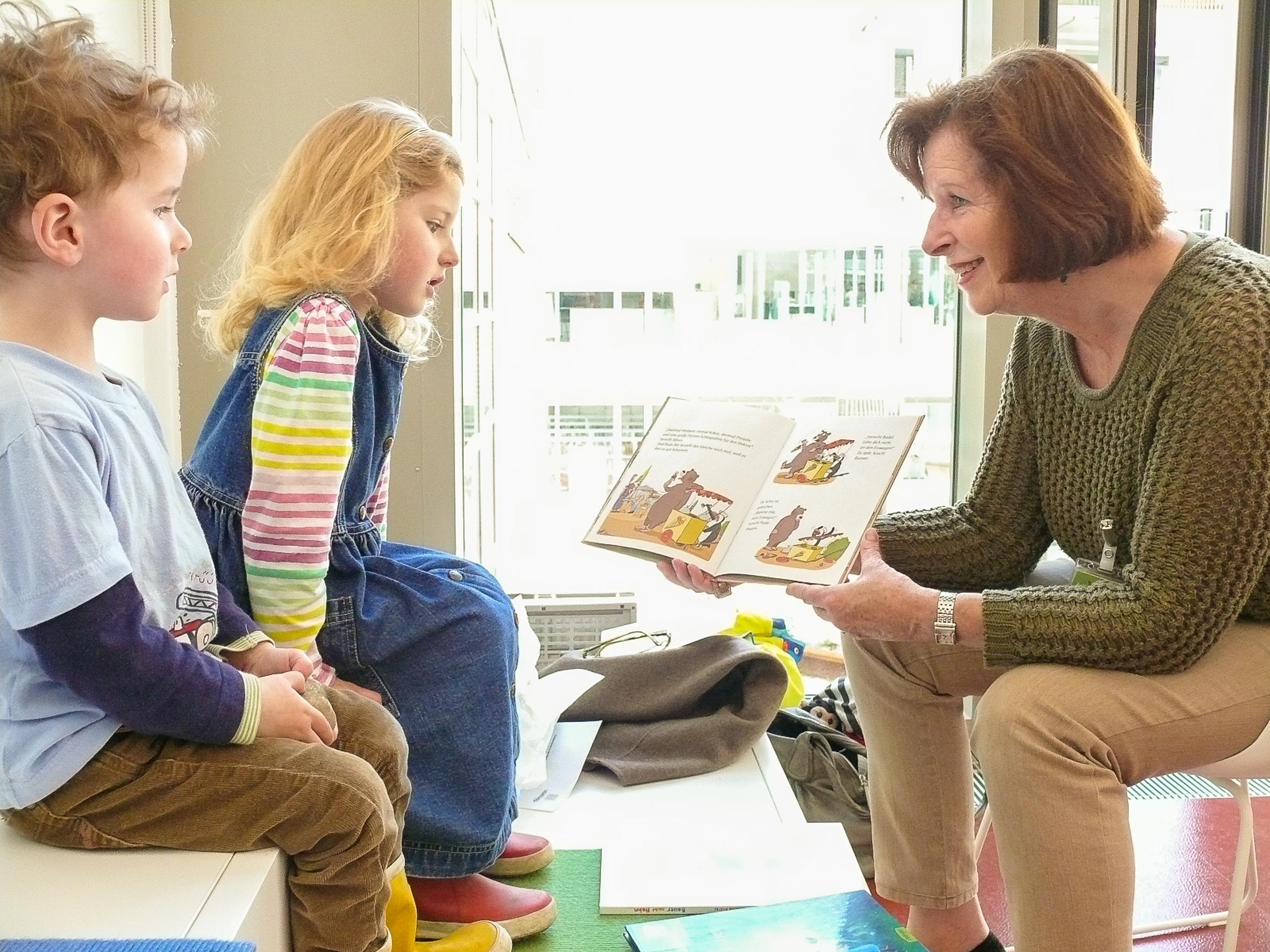 Brigitte Erhardt liest ihren beiden kleinen Stammzuhörern Quirin und Maria vor